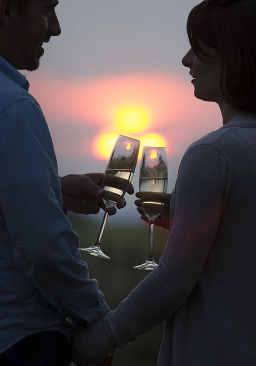 Couple toasting champagne at sunset