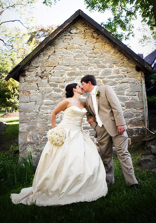Couple kissing in front of a cobblestone building
