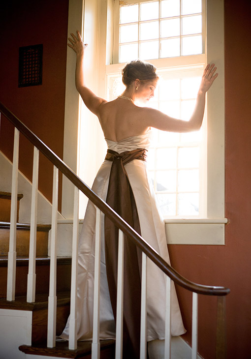 Bride by the window on the stairs