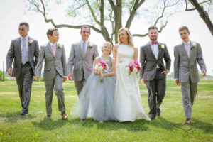 Bridal party walking across the green grass