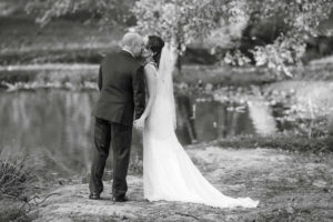 Bride and groom kissing by the pond