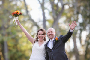 Bride and groom smiling with hands in the air