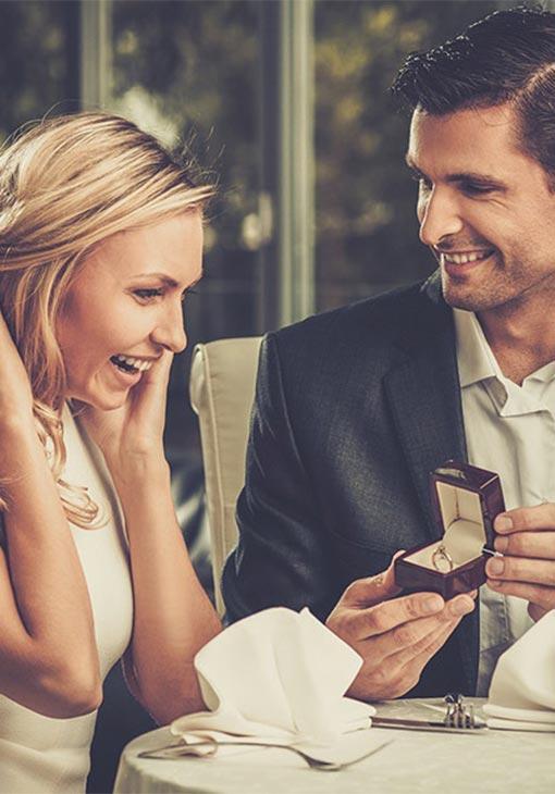 Man proposing to girl during romantic dinner