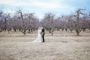 Wedding couple kissing in front of trees