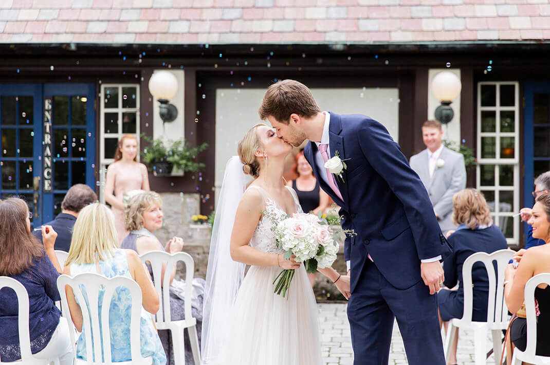 Couple kissing during at outdoor wedding reception